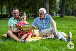 Vater, Kind und Wahl-Opi sitzen auf einer Decke und lesen ein Buch